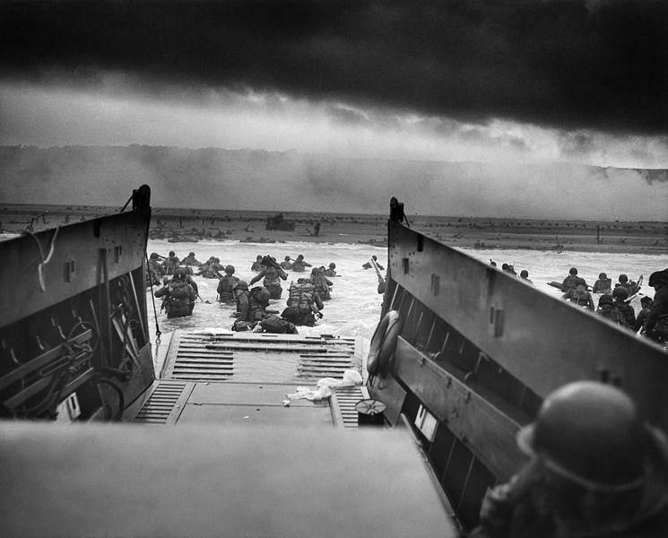 Seconde Guerre mondiale, Europe, France. « Entre les dents de la mort — Les troupes américaines pataugent dans l'eau sous les balles nazies. ». Photo prise vers 08:30 le matin du 6 juin 1944. Photo DP/United States Coast Guard
